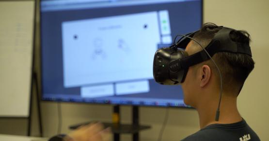 A student in China works with a virtual reality glove by Noitom.